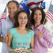 Family outdoors on fourth of July with flags and cookies smiling - Stock Photo