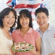 Family outdoors on fourth of July with flags and cookies smiling — Stok Fotoğraf #4781412
