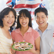 Family outdoors on fourth of July with flags and cookies smiling — Stockfoto