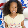 Foto de Stock  : Young girl on fourth of July with balloons and cookies smiling