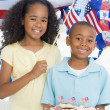 Brother and sister on fourth of July with flag and cookies smili — Stockfoto