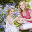 Mother and daughter on Easter looking for eggs outdoors smiling — Stock Photo