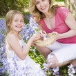 Stock Photo: Mother and daughter on Easter looking for eggs outdoors smiling