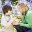 Mother and son on Easter looking for eggs outdoors smiling - Stock Photo