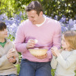 Stock Photo: Father and two young children on Easter looking for eggs outdoor