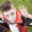 Young boy outdoors wearing vampire costume on Halloween — Stock Photo