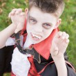 Foto Stock: Young boy outdoors wearing vampire costume on Halloween
