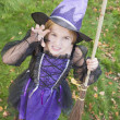 Young girl outdoors in witch costume on Halloween — Stock Photo #4781441