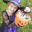 Foto Stock: Young girl outdoors in witch costume on Halloween holding candy