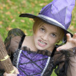 Young girl outdoors in witch costume on Halloween — Stock Photo
