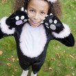 Young girl outdoors in cat costume on Halloween - Stockfoto