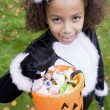 Young girl outdoors in cat costume on Halloween holding candy — Stock Photo