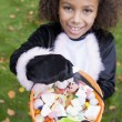 Young girl outdoors in cat costume on Halloween holding candy - Stock Photo