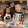 Four young friends and a woman at Halloween eating treats and sm - Foto Stock
