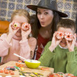 Stok fotoğraf: Mother and two children at Halloween playing with treats and smi