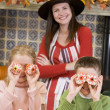 Mother and two children at Halloween playing with treats and smi — Stock Photo