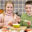 Stockfoto: Brother and sister at Halloween making treats and smiling