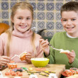 Stock Photo: Brother and sister at Halloween making treats and smiling