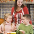 Foto Stock: Mother and two children at Halloween making treats and smiling
