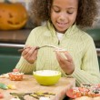Young girl at Halloween making treats and smiling — Stock Photo #4781477