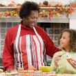 Stock Photo: Grandmother and granddaughter making Halloween treats and smilin