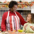 Grandmother and granddaughter making Halloween treats and smilin — Stock Photo
