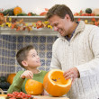Father and son carving jack o lanterns on Halloween and smiling - Stock Photo