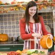 Woman carving jack o lantern on Halloween and smiling — Stock Photo