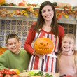 Mother and two children carving jack o lanterns on Halloween and — Stockfoto #4781497