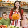 Mother and two children carving jack o lanterns on Halloween and — Photo #4781497