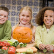Foto Stock: Three young friends on Halloween with jack o lantern and food sm