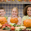 Foto Stock: Three young friends on Halloween with jack o lanterns and food s