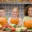 Stok fotoğraf: Three young friends on Halloween with jack o lanterns and food s