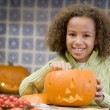 Young girl on Halloween with jack o lantern smiling — Foto de stock #4781504