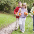 Three young friends walking on path with pumpkins smiling — Stock Photo