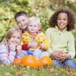 Three young friends with baby sitting on grass with pumpkins smi - Stockfoto