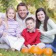 Family sitting on grass with pumpkins smiling — Stock Photo #4781514