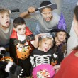 Foto Stock: Six children in costumes trick or treating at woman's house