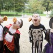 Four young friends on Halloween in costumes eating donuts hangin — Zdjęcie stockowe #4781524
