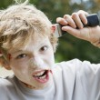 Young boy with scary Halloween make up and plastic knife through — Stock Photo