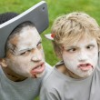 Foto Stock: Two young boys with scary Halloween make up and plastic knives t