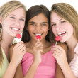 Three girl friends with suckers smiling — Stock Photo