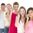 Stock Photo: Row of five friends on cellular phones smiling
