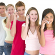 Row of five friends on cellular phones smiling — Stock Photo