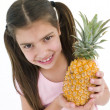 Young girl holding pineapple and smiling — Stockfoto