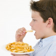 Young boy eating French fries — Stock Photo #4781904