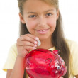 Young girl putting coin into piggy bank smiling — Stock Photo #4781933