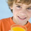 Young boy with glass of orange juice smiling — Stock Photo #4781976