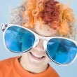 Young boy wearing clown wig and sunglasses smiling — Stock Photo