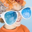Young boy wearing clown wig and sunglasses smiling - Stock Photo